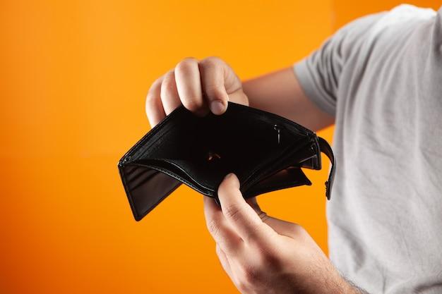 Mężczyzna pokazujący pusty portfel na pomarańczowym tle