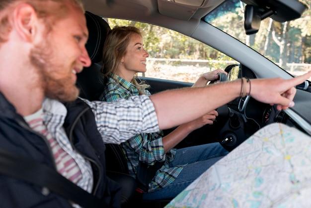 Mężczyzna pokazujący swojej dziewczynie, gdzie zatrzymać samochód na kemping