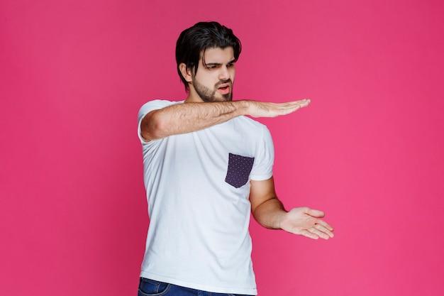 Mężczyzna pokazujący szacunkowe wymiary paczki.