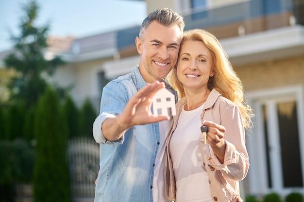 Mężczyzna pokazujący znak domu i żonę z kluczem