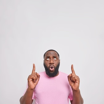 Mężczyzna pokazuje banery powyżej na przestrzeni kopii pokazuje nowy rabat ubrany w casualową różową koszulkę