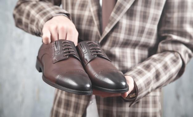 Mężczyzna pokazuje brązowe buty. moda. styl życia
