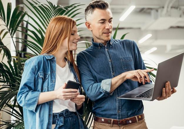 Mężczyzna pokazuje coś na laptopie swojemu współpracownikowi