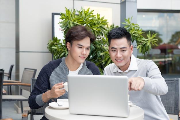 Mężczyzna pokazuje dokument swojemu koledze podczas picia kawy w mieście