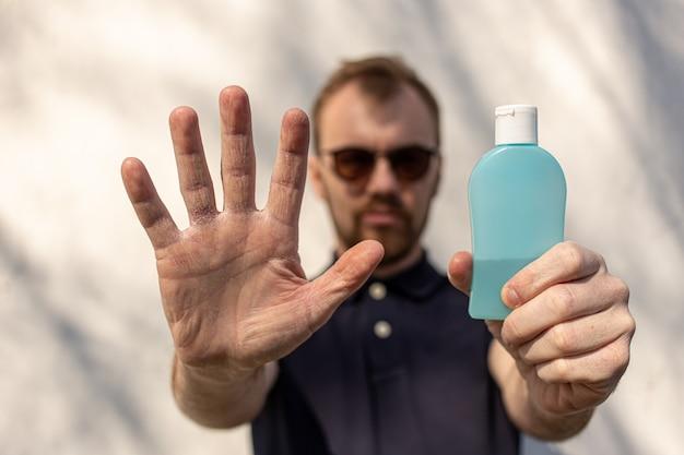 Mężczyzna pokazuje jedną rękę i trzyma butelkę antybakteryjnego środka odkażającego