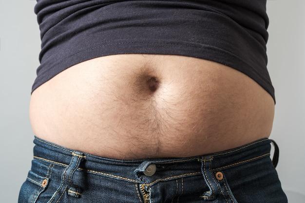 Mężczyzna pokazuje jego tłuszcz na żołądku