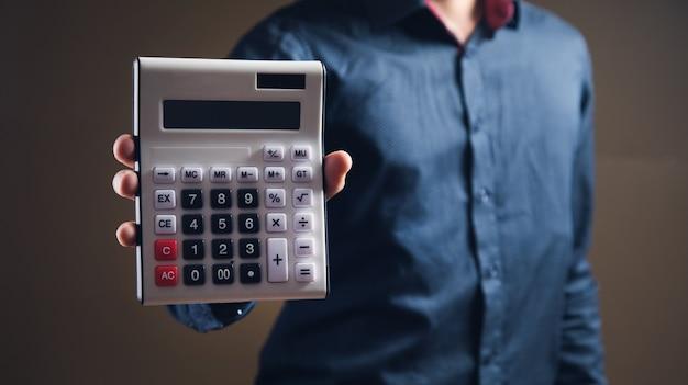 Mężczyzna pokazuje kalkulator na brązowej powierzchni