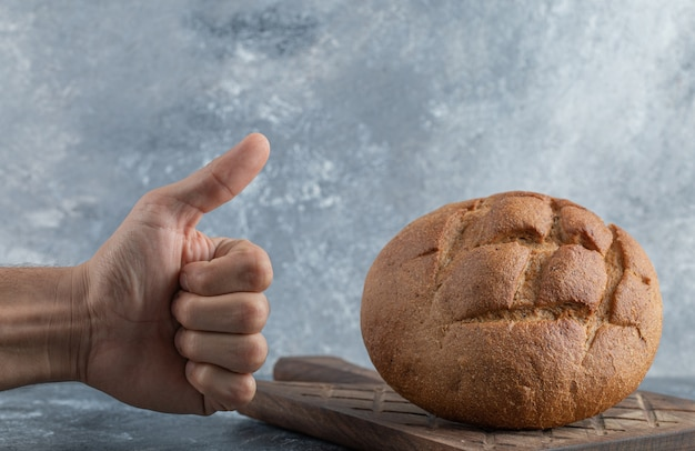 Mężczyzna pokazuje kciuk do bochenka chleba żytniego. wysokiej jakości zdjęcie