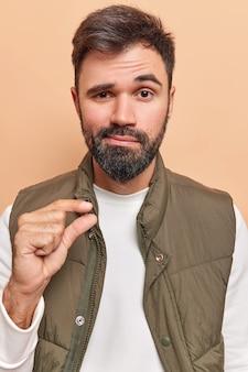 Mężczyzna pokazuje mały gest kształtuje coś drobniutkiego narzeka na brak czasu unosi brwi ubrany niedbale pozuje w pomieszczeniu