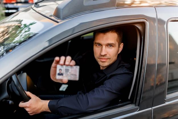 Mężczyzna pokazuje policjantowi prawo jazdy. biznesmen patrzeje kamerę