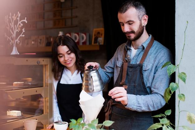 Mężczyzna pokazuje pracownikowi jak nalewać kawę w filtrze