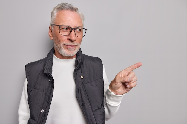 Mężczyzna pokazuje promocję przedstawia nowy produkt z pewnym siebie wyrazem twarzy nosi okulary swobodny sweter i kamizelkę demonstruje pustą przestrzeń na szaro