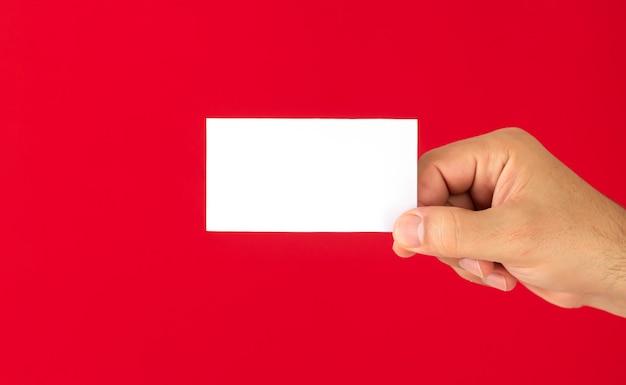 Mężczyzna pokazuje pustą białą wizytówkę na białym tle na czerwonym tle