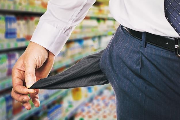 Mężczyzna pokazuje pustą kieszeń na sklepie koncepcję braku pieniędzy na zakupy