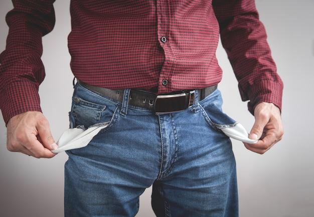 Mężczyzna pokazuje puste kieszenie. bankructwo.