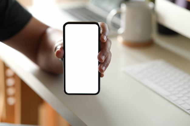 Mężczyzna pokazuje pustego ekranu telefon komórkowego przy biurem