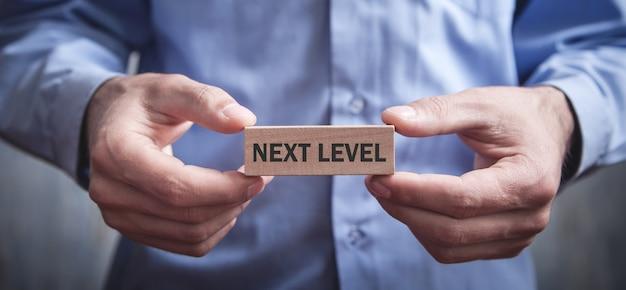 Mężczyzna pokazuje słowo następnego poziomu na drewnianym klocku.