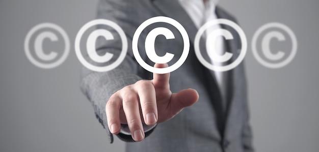 Mężczyzna pokazuje symbol praw autorskich. własność intelektualna