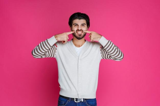 Mężczyzna pokazuje zęby palcami wskazującymi.
