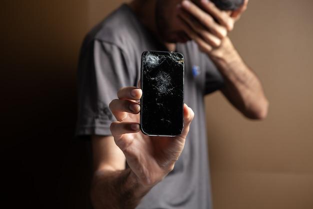 Mężczyzna pokazuje zepsuty ekran telefonu na brązowym tle