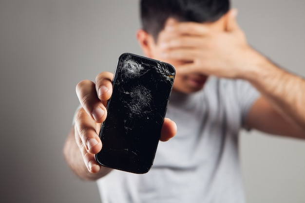 Mężczyzna pokazuje zepsuty ekran telefonu na szarym tle