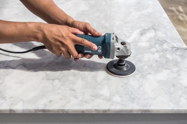 Mężczyzna polerowniczy marmuru kamienia stół małym kąta ostrzarzem