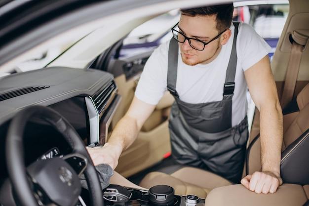 Mężczyzna polerujący samochód wewnątrz w serwisie samochodowym