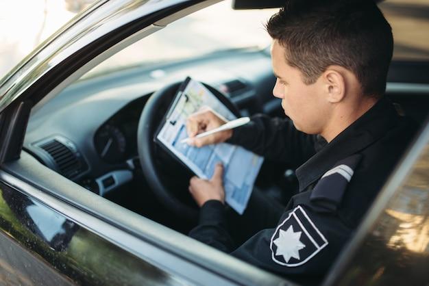 Mężczyzna policjant siedzi w samochodzie i wypisuje mandat