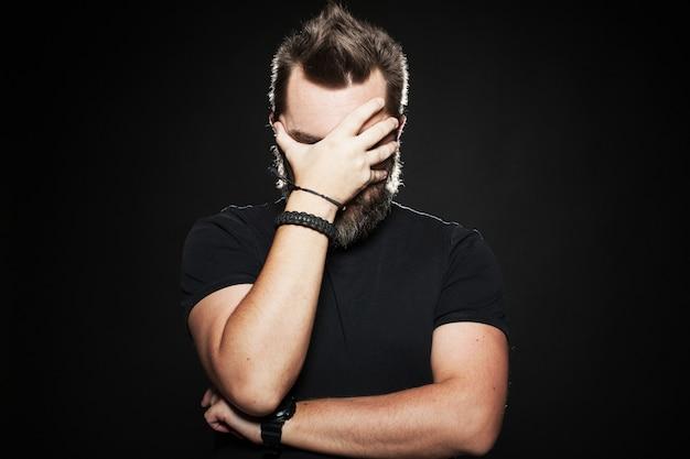 Mężczyzna położył dłoń na twarzy w studio.