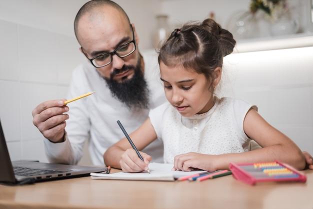 Mężczyzna pomaga córce w odrabianiu prac domowych.