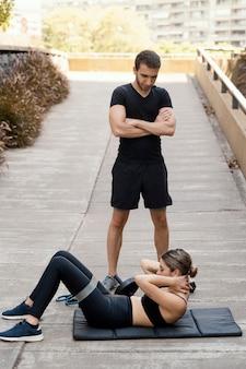 Mężczyzna pomaga kobiecie ćwiczyć na świeżym powietrzu