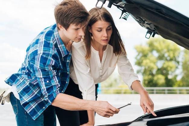 Mężczyzna pomaga kobiecie naprawić jej samochód