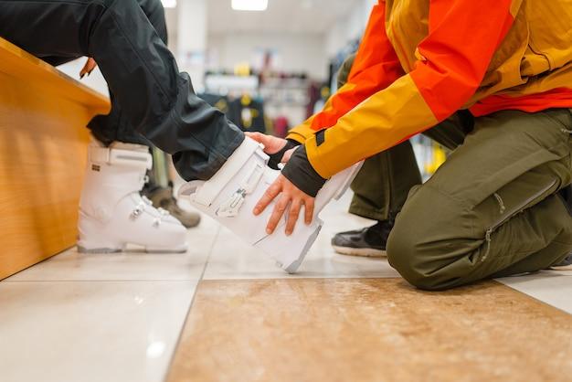 Mężczyzna pomaga kobiecie przymierzyć buty narciarskie, zakupy