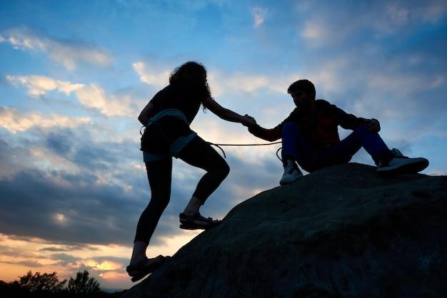 Mężczyzna pomaga kobiecie w górę krawędzi góry