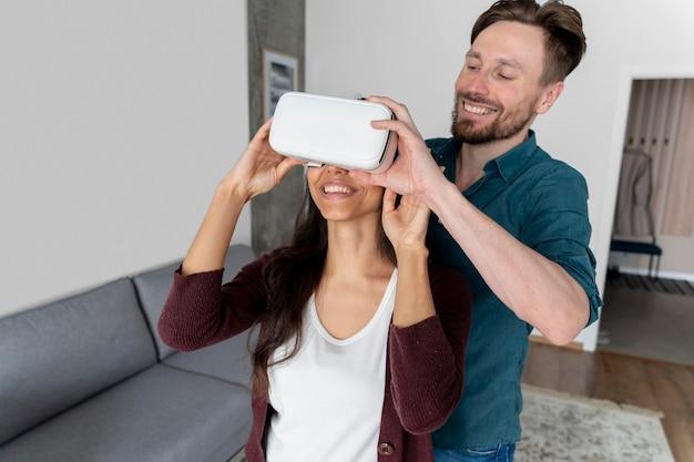 Mężczyzna pomaga kobiecie założyć zestaw słuchawkowy wirtualnej rzeczywistości