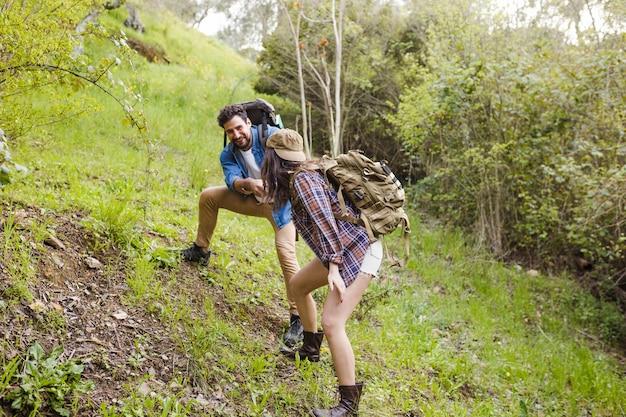 Mężczyzna pomaga kobieta wspinać się wzgórze