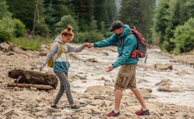 Mężczyzna pomaga młodej kobiecie przekroczyć górską rzekę podczas wędrówek razem