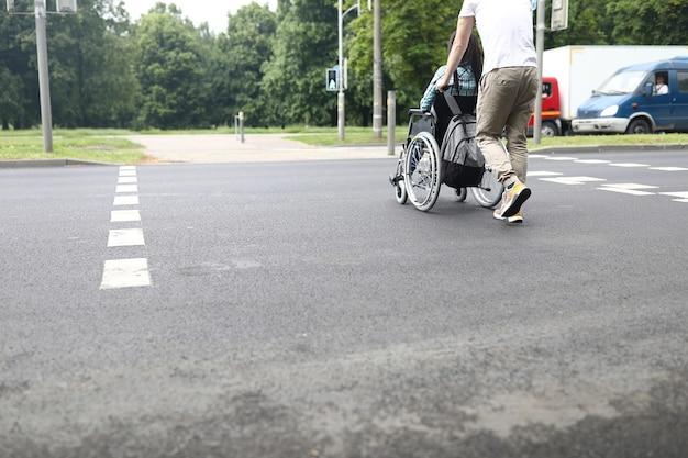 Mężczyzna pomaga niepełnosprawnej kobiecie poruszać się na wózku inwalidzkim na drodze