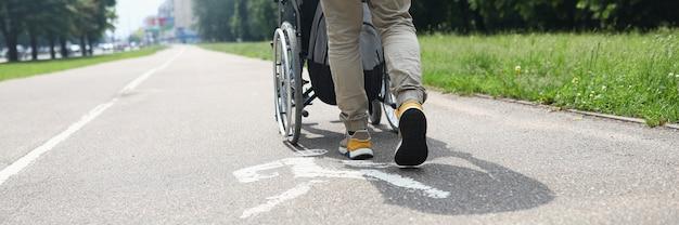 Mężczyzna pomaga osobie niepełnosprawnej na wózku inwalidzkim chodzić po chodniku
