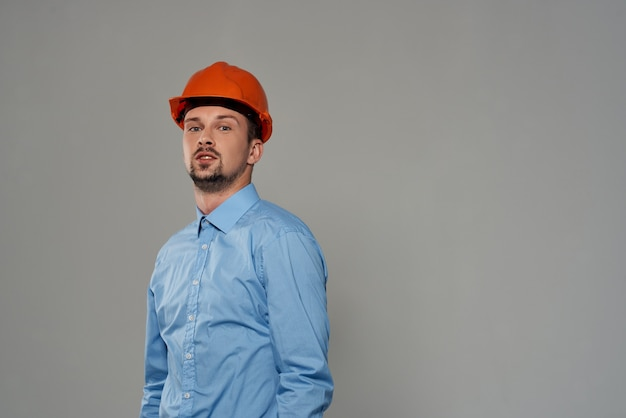 Mężczyzna pomarańczowy kask inżynier bezpieczeństwa na białym tle