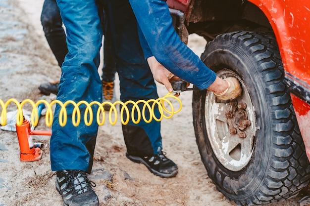 Mężczyzna pompuje koło pneumatyczne ze sprężarką