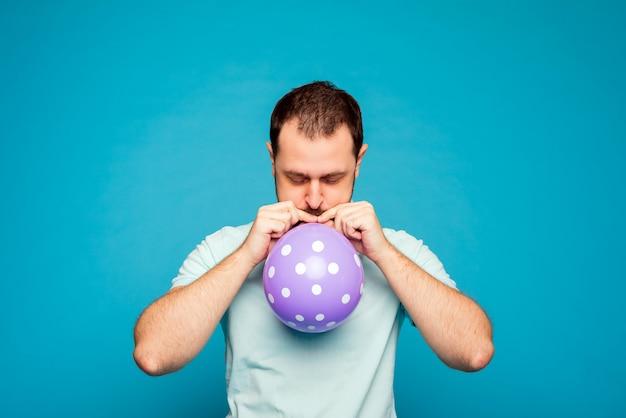 Mężczyzna pompuje purpurowego balon