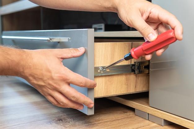 Mężczyzna poprawia szufladę. samodzielny montaż mebli. młoda złota rączka w ogólnej instalacji szuflady w kuchni