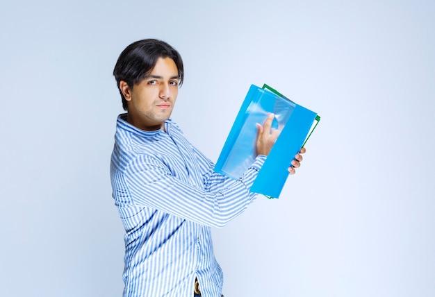 Mężczyzna poprawiający błędy i zwracający foldery raportów swojemu koledze. zdjęcie wysokiej jakości