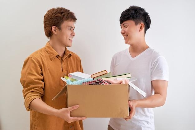 Mężczyzna posiadający książkę i ubrania oddania pudełko. koncepcja darowizny.
