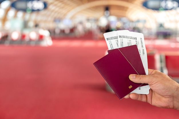 Mężczyzna posiadający paszporty i paszport pokładowy na lotnisku. zdjęcie wysokiej jakości