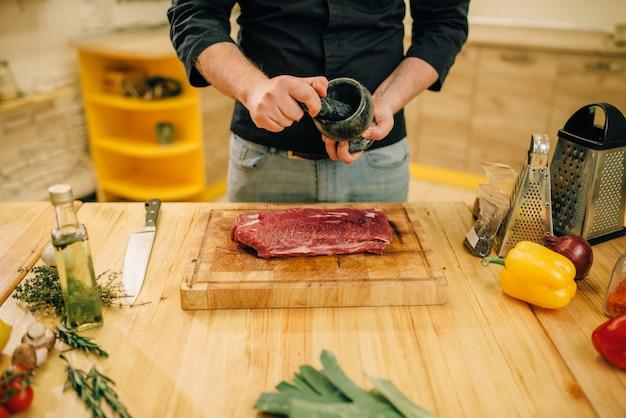 Mężczyzna posypuje surowe mięso przyprawami