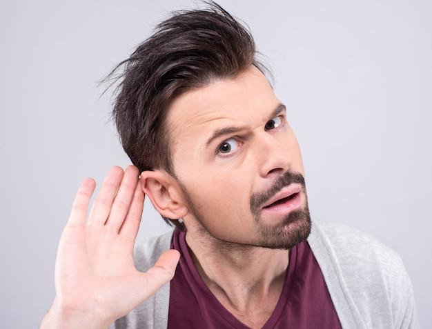 Mężczyzna potajemnie słucha podczas prywatnej rozmowy.