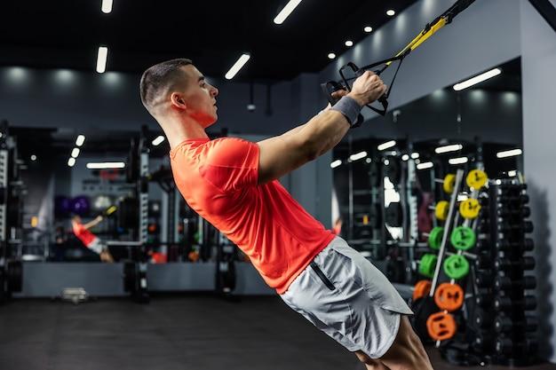 Mężczyzna powoli i w równowadze wykonuje ćwiczenia na ramiona i całe ciało na pasach fitness trx i trzyma za rączki