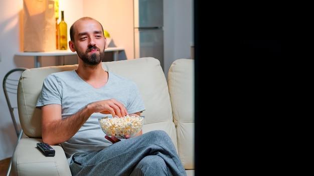 Mężczyzna późno w nocy w swoim mieszkaniu ogląda rozrywkę w telewizji